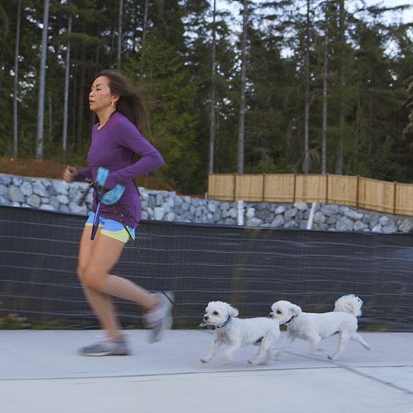 Josephine running on sidewalk with her two dogs