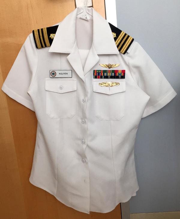 White uniform shirt hanging on door