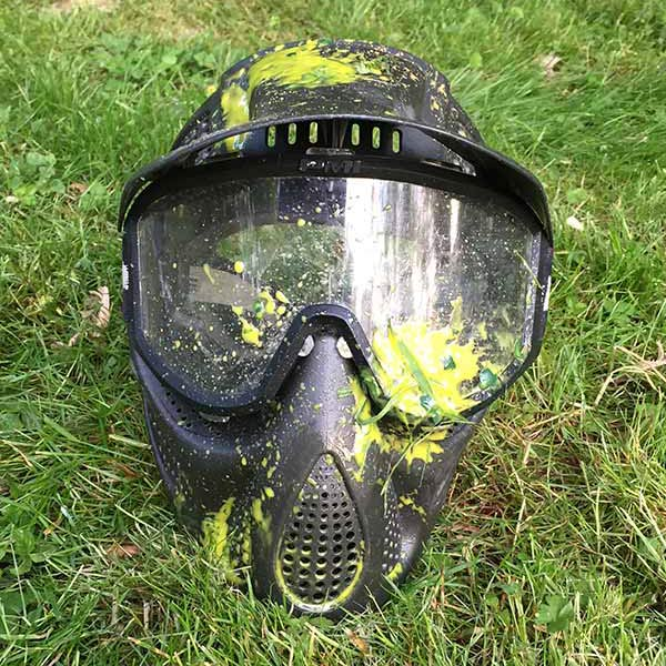 paintball mask in grass covered in paint