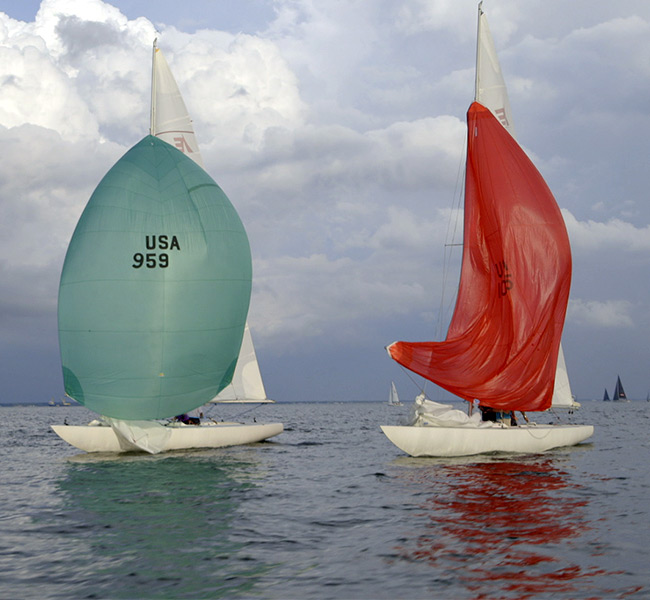 three sailboats in a race with their spinnakers up