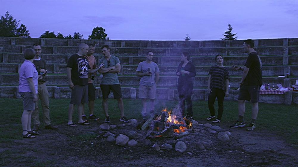 Sara and her friends standing in front of a fire