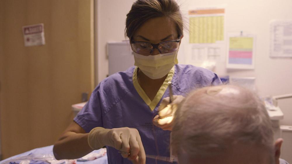 Josephine applying sutures to patient's shoulder