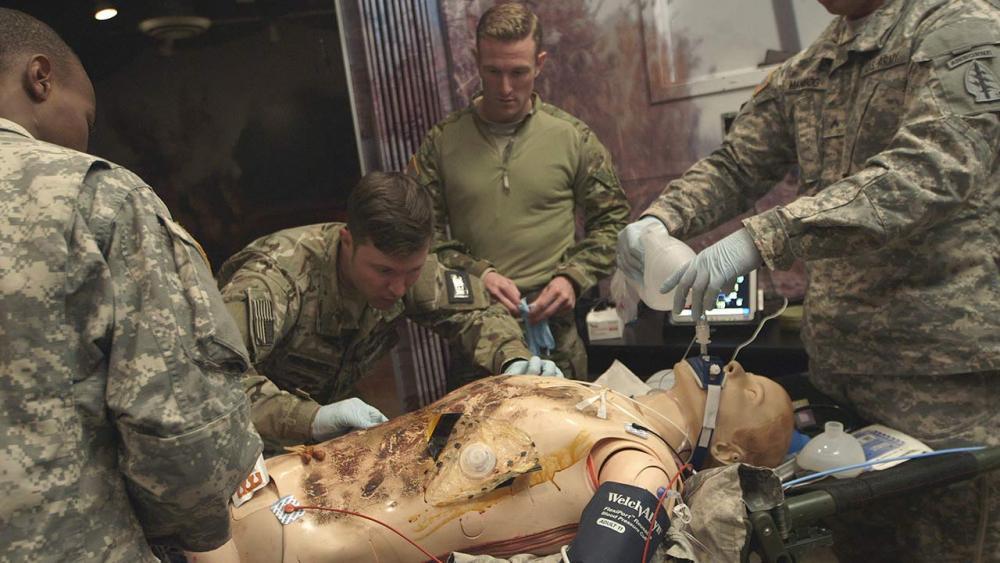 medics performing an escharotomy on simulation mannequin