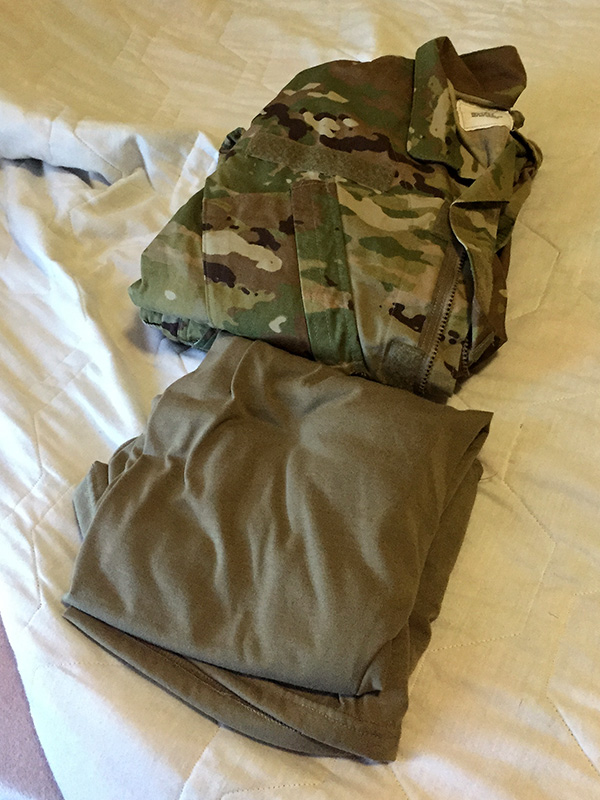 Military uniforms folded on bed