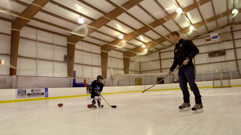 Hunter passes his son the puck on ice rink