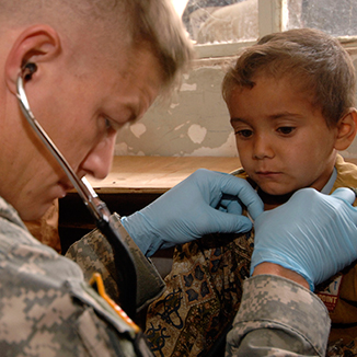 A military physician examines a child.