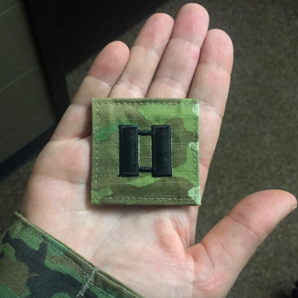 Sara holding a green square patch in the palm of her hand