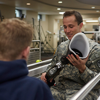 A military physician holds a prosthetic leg.