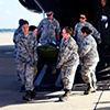 Air Force medical professionals carry a stretcher out of a plane during a training exercise.