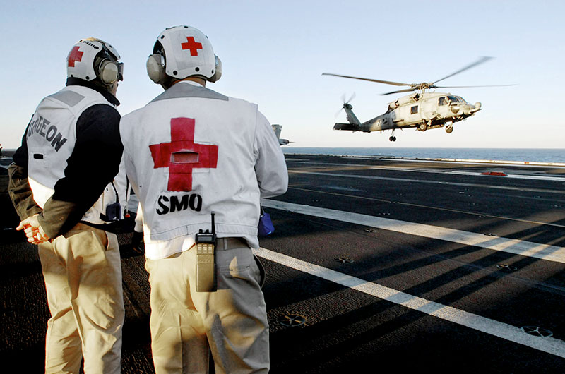 Two military medical professionals watch a helicopter land.