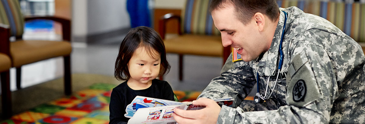 A military physician reads to a young patient.