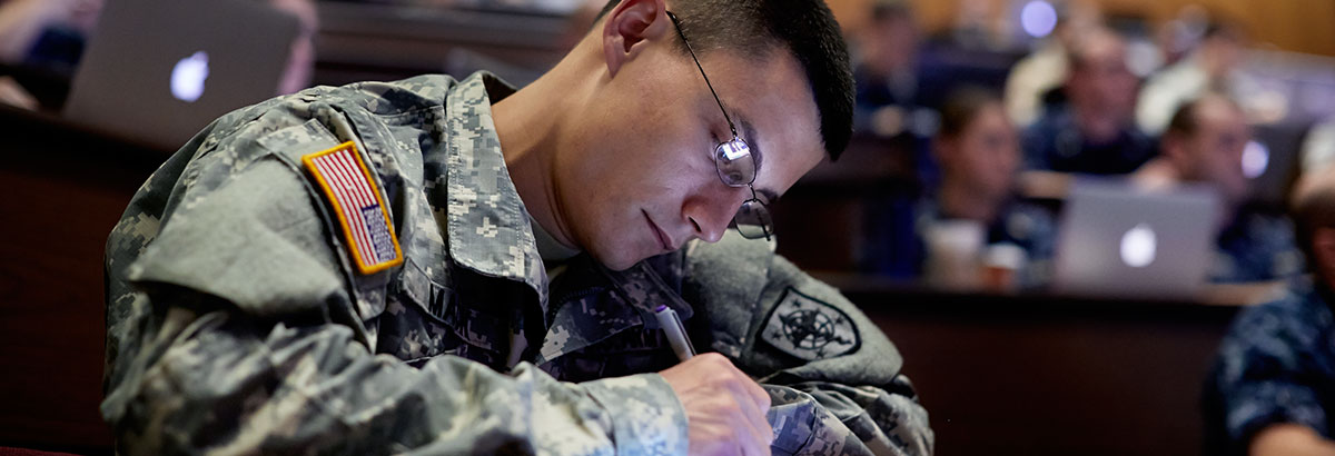 A military medical student takes notes in class.