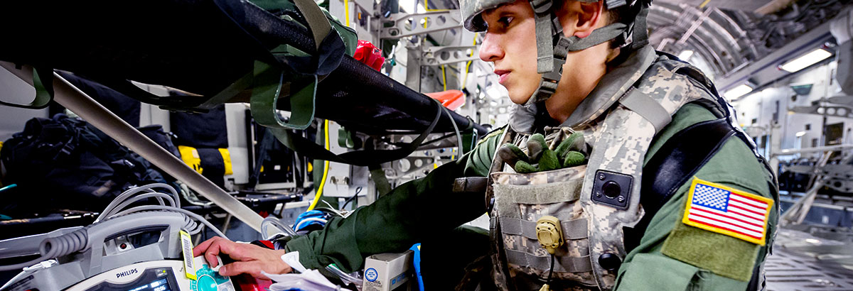A military medical professional inspects equipment on a plane.