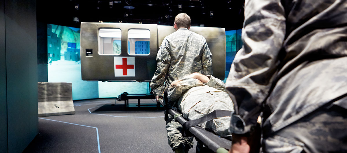 Military medical students carry a patient toward a simulator.