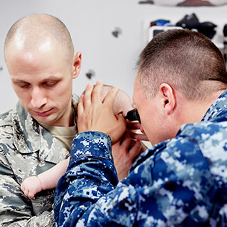 A military physician evaluates the child of a service member.