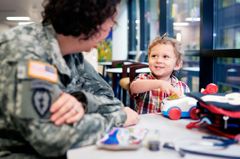 A military physician brightens a young patient's day.